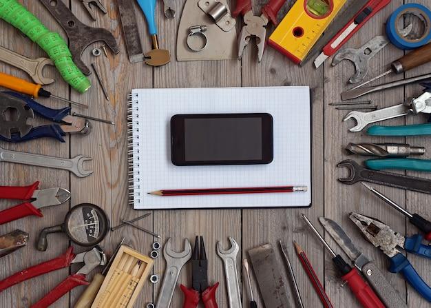 Jogo das ferramentas em um assoalho de madeira com um caderno e um telefone móvel no centro.