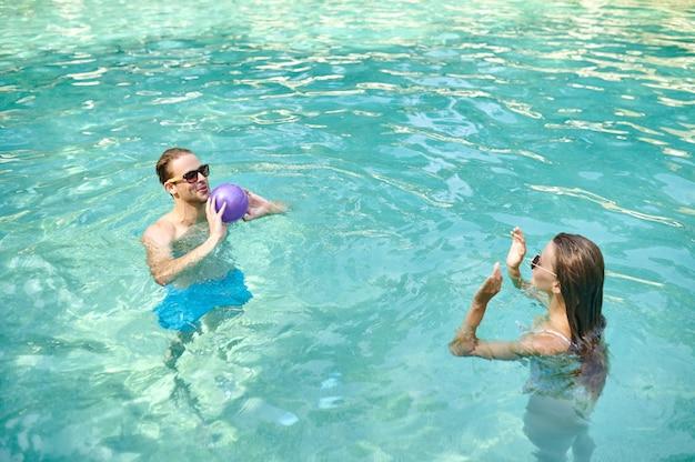 Jogo de água. um homem e uma mulher jogando bola em uma piscina