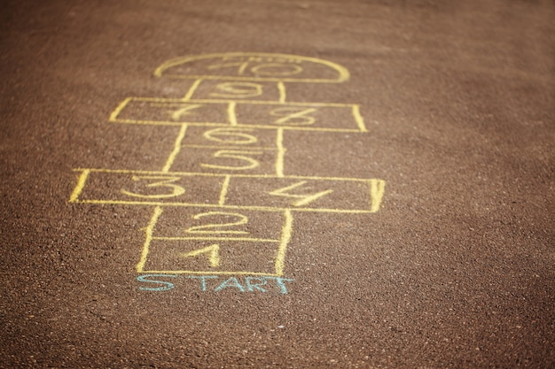 Jogo de amarelinha sendo desenhado com um giz no asfalto. jogo de rua popular