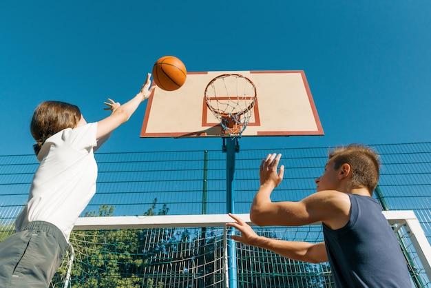 Jogo de basquete de streetball com dois jogadores, adolescentes menina e menino