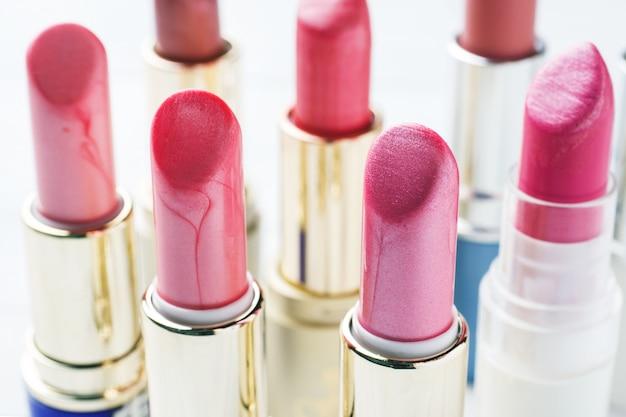 Jogo de batons cor-de-rosa coloridos no fundo branco. cosméticos femininos. foco seletivo.