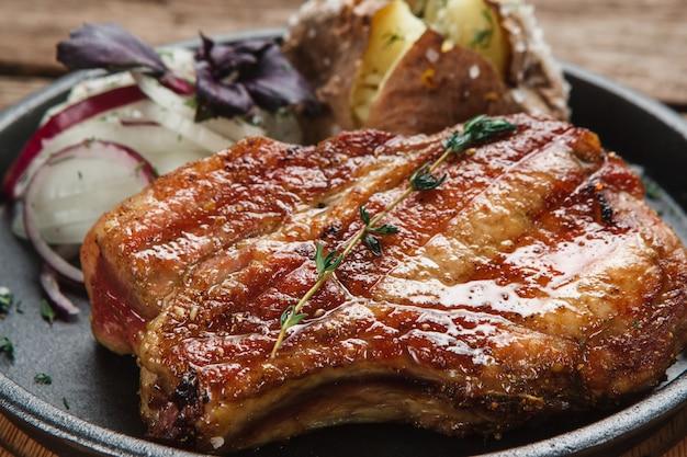 Jogo de beaf grelhado suculento servido com batata cozida e anéis de cebola, vista do close up. cozinha americana.