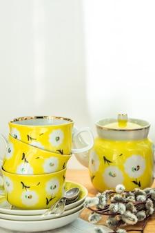 Jogo de chá amarelo bonito com copos empilhados, pires e pote, ornamento floral, brunch de páscoa