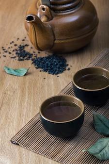 Jogo de chá asiático e folhas de chá em uma mesa de madeira. conceito de chá.