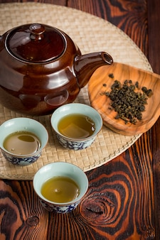 Jogo de chá asiático na esteira de bambu