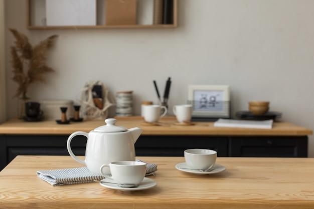Jogo de chá branco para beber chá na mesa servida na cozinha