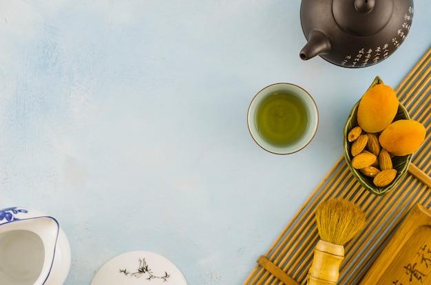 Jogo de chá chinês com frutas secas e escova no plano de fundo texturizado branco