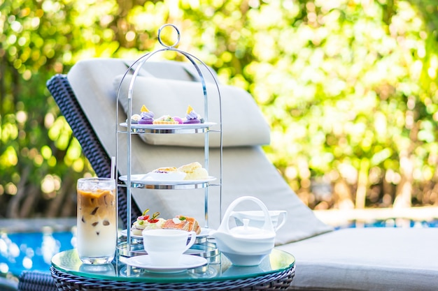 Jogo de chá da tarde com café com leite e chá quente na mesa perto da cadeira ao redor da piscina