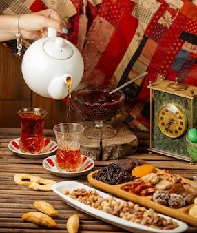 Jogo de chá para 2 pessoas com frutas secas e doces, chaleira branca, mesa de madeira