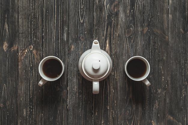 Jogo de chá para o par. copos e bule na tabela rústica preta.