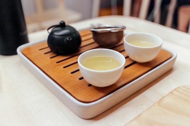 Jogo de chá verde em copos na pequena placa de madeira com chaleira e treinador.