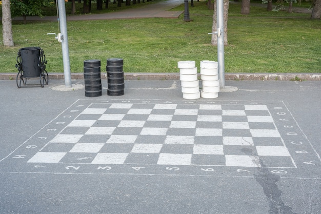 Jogo de damas. xadrez preto e branco gigantesco no asfalto.