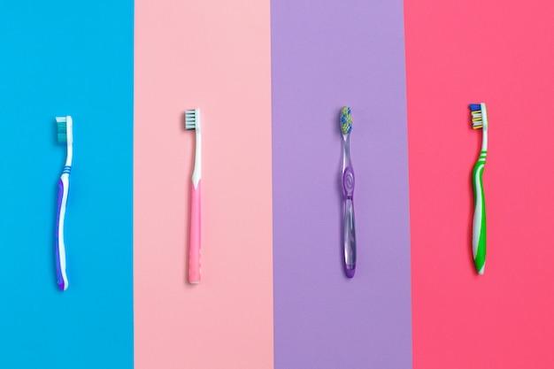 Jogo de escovas de dentes diferentes no fundo da cor.