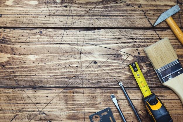 Jogo de ferramentas diferentes do reparo no fundo de madeira com espaço da cópia.