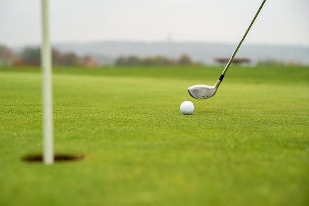 Jogo de golfe no campo verde com bola e taco