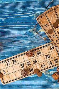 Jogo de loteria com cartas e barris de madeira em um fundo azul de madeira