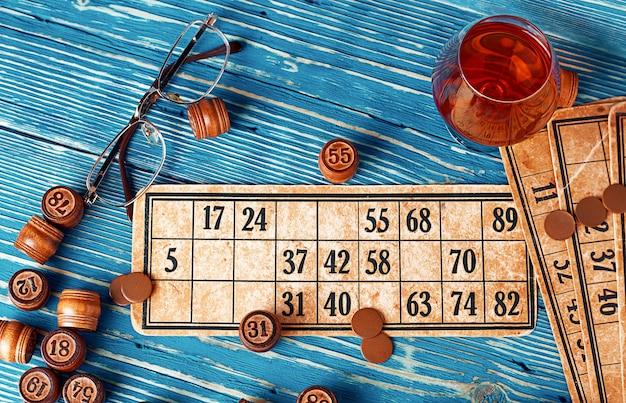 Jogo de loteria com cartas e barris de madeira em uma mesa de madeira azul
