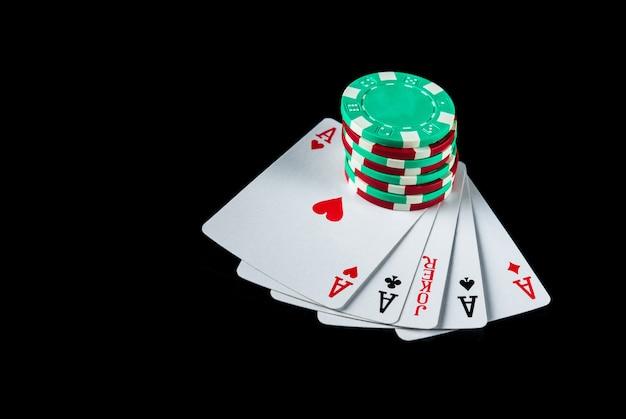 Jogo de pôquer com combinação de cinco tipos de fichas e cartas na mesa preta