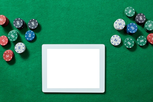 Jogo de pôquer online com tablet digital e pilhas de fichas, vista superior. conceito de jogos de azar online, pôquer, cassino virtual.