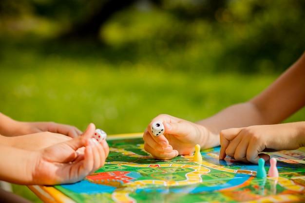 Jogo de tabuleiro e conceito de lazer de crianças. as crianças estão brincando. pessoas segurando figuras na mão. chips em crianças brincam. conceito de jogos de tabuleiro. dados, fichas e cartões. jogos de festa