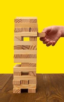 Jogo de tabuleiro ou torre em uma mesa de madeira e um fundo amarelo