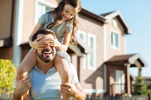 Jogo divertido. filha pequena sentada sobre os ombros de seu pai feliz e cobrindo os olhos com as mãos