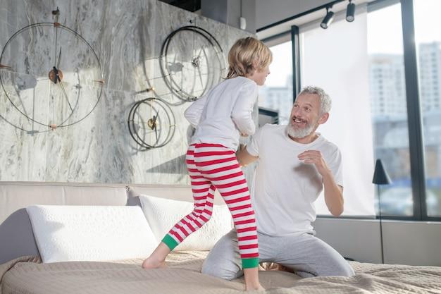 Jogo divertido. pai alegre e energético de cabelos grisalhos e filho fazendo quadrinhos na cama em casa