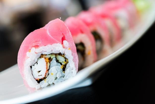Jogo do sushi em uma fileira em uma placa
