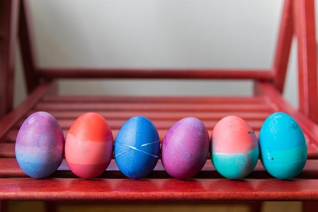 Jogo dos ovos da páscoa que estão no fundo vermelho da cadeira. ovos brilhantes festivos coloridos pintados abstratamente em azul, rosa, verde e roxo.