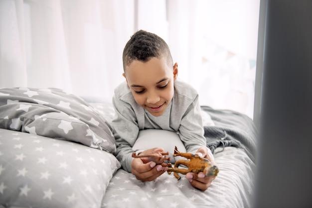 Jogo educativo. garoto afro-americano atraente posando na cama enquanto brinca com brinquedos de dinossauros