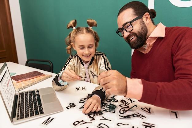 Jogo educativo. linda garota de cabelos louros com pulseiras na mão e se sentindo envolvida enquanto joga jogos de palavras com a professora