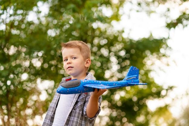 Jogo novo do menino com airplaine do brinquedo nas mãos. criança feliz é brincar no parque ao ar livre.