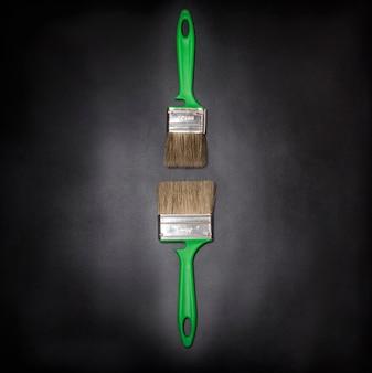 Jogo plano, dois pincéis verdes em um plano de fundo texturizado preto com vinheta.
