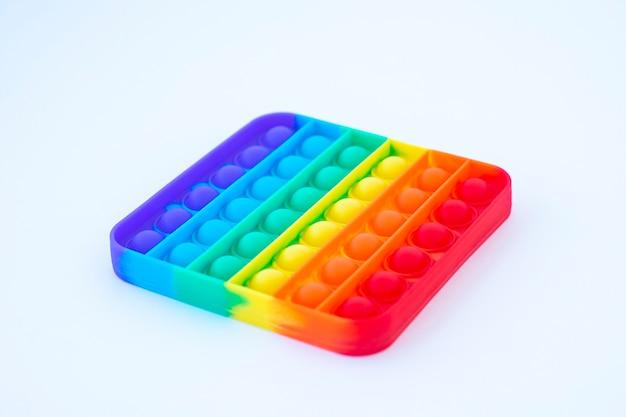 Jogo poppit colorido do arco-íris. close-up de silicone fidget em um fundo branco.