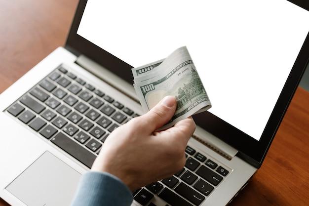 Jogos de azar em cassino online homem segurando dinheiro e fazendo apostas virtuais usando laptop