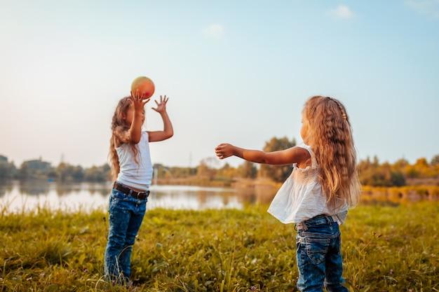 Jogos de bola. menina brincando com bola com a irmã no parque de verão. crianças se divertindo ao ar livre.