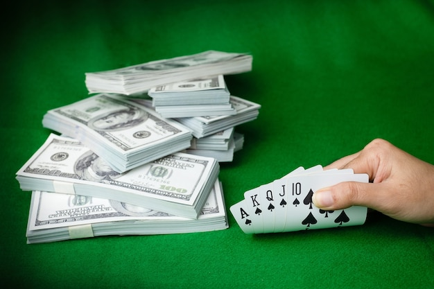 Jogos de casino de pôquer royal straight flush e a pilha de notas de 100 dólares americanos