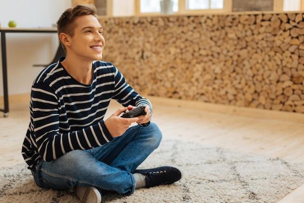 Jogos de jogar. jovem bonito e inspirado de cabelos louros sorrindo e segurando um controle remoto para jogar enquanto está sentado no chão