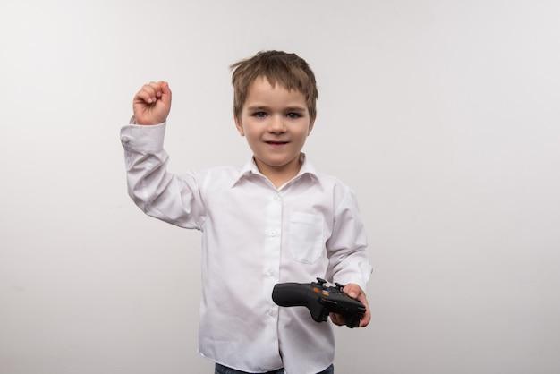 Jogos eletronicos. menino bonito e fofo segurando um console de jogo enquanto joga jogos eletrônicos