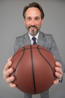 Jogue basquete, seja feliz. feliz empresário segura bola de basquete. plano de fundo cinza do treinador de basquete. treinador de basquete. competição empresarial e desportiva. jogo competitivo. jogar difícil.