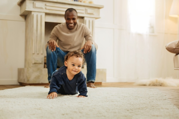 Jogue comigo. homem afro-americano vigoroso de cabelos escuros rindo e vendo seu filho feliz rastejando no chão