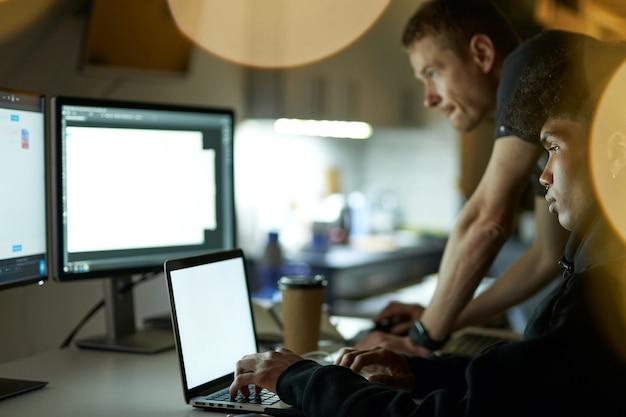 Jogue-se no trabalho dois caras na frente de muitos monitores de computador trabalhando tarde da noite