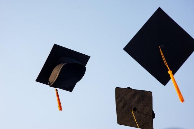 Jogue um chapéu preto de graduados no céu.