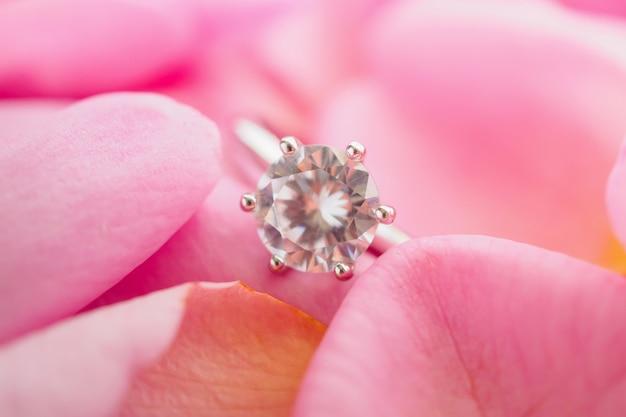 Joia com anel de diamante em linda pétala de rosa rosa