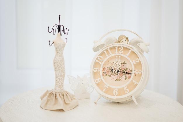 Jóias de casamento das mulheres (brincos, pulseiras) em um relógio, foco seletivo