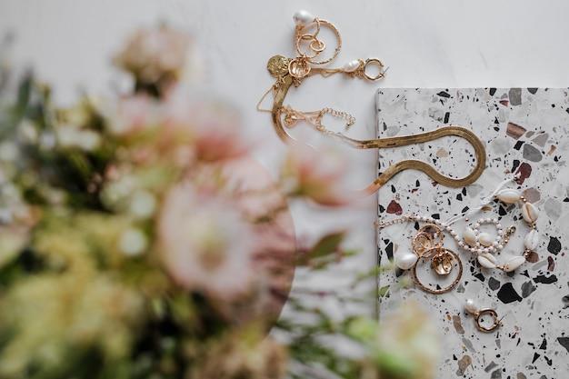 Joias de ouro com buquê de flores Foto Premium