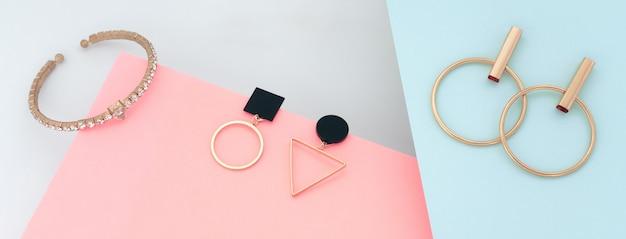 Jóias de ouro modernas sobre fundo azul e rosa