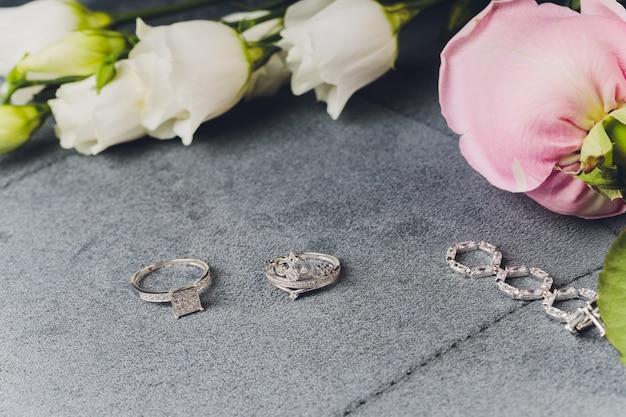 Jóias de prata e pedra branca. pulseiras de ágata, anéis de prata e brincos em uma superfície clara, vista superior, configuração plana, cópia espaço. jóias femininas em uma superfície cinza com espaço livre para texto.