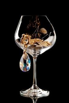 Joias e moedas de euro no copo de vinho quebrado