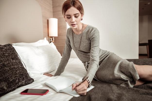 Joias elegantes. linda empresária inteligente usando joias elegantes e fazendo anotações